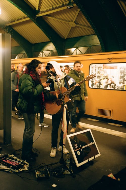 Musicians playing guitar on subway station