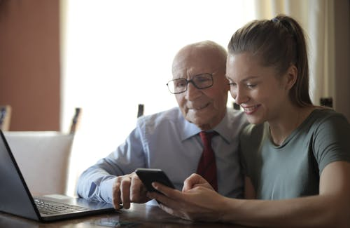 Positive senior man in formal shirt and eyeglasses and smiling young granddaughter sharing mobile phone while sitting near laptop at table
