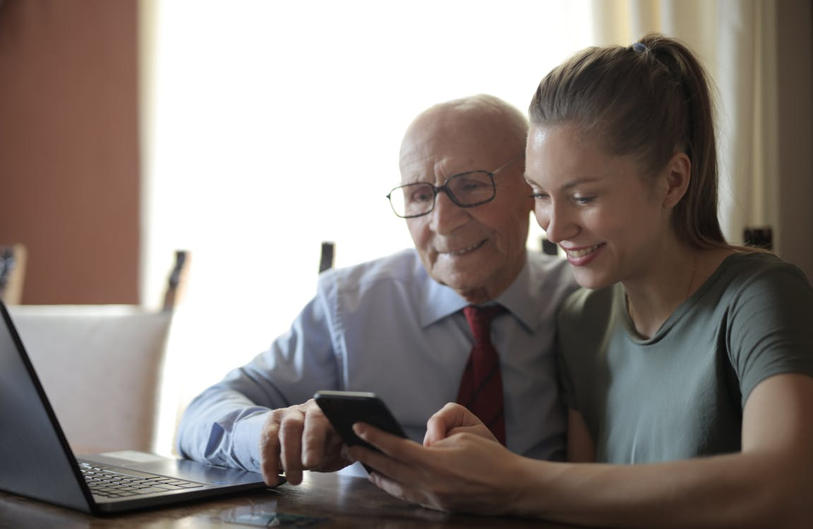 Positive senior man and smiling young woman watching smartphone while sitting at table
