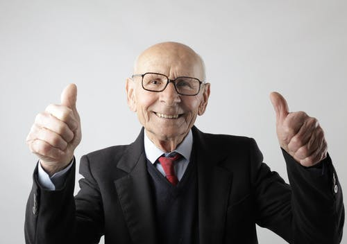Positive senior man in eyeglasses showing thumbs up and looking at camera