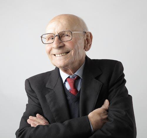 Portrait Photo of Man in Black Suit Jacket Wearing Eyeglasses Smiling