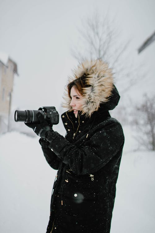 Woman in Black and Brown Parka Jacket Holding Black Dslr Camera