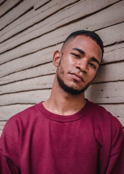 木製の壁にもたれて思いやりのある若い民族の男
