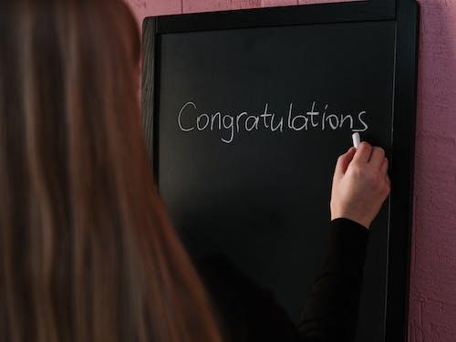 Woman in Black Long Sleeve Shirt Writing on the Chalkboard