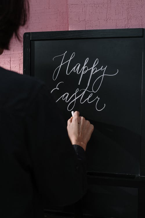 Person Writing on Chalkboard