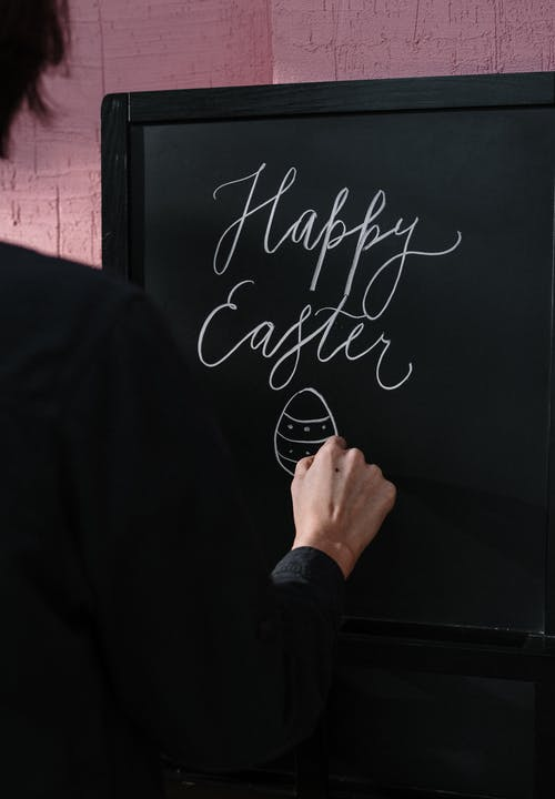 Person in Black Long Sleeve Shirt Holding Black Chalk Board