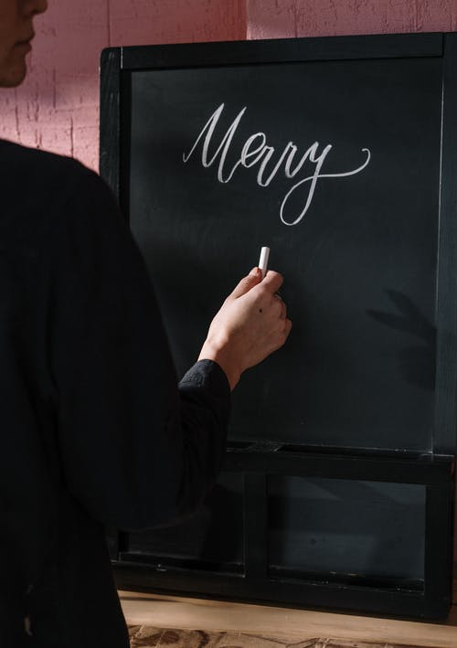 Person in Black Long Sleeve Top Writing on Black Board
