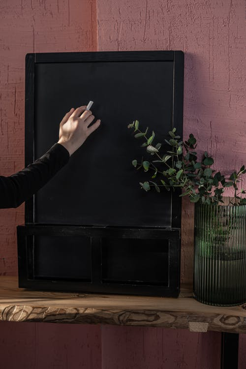 Person Holding White Chalk Next to Black Board