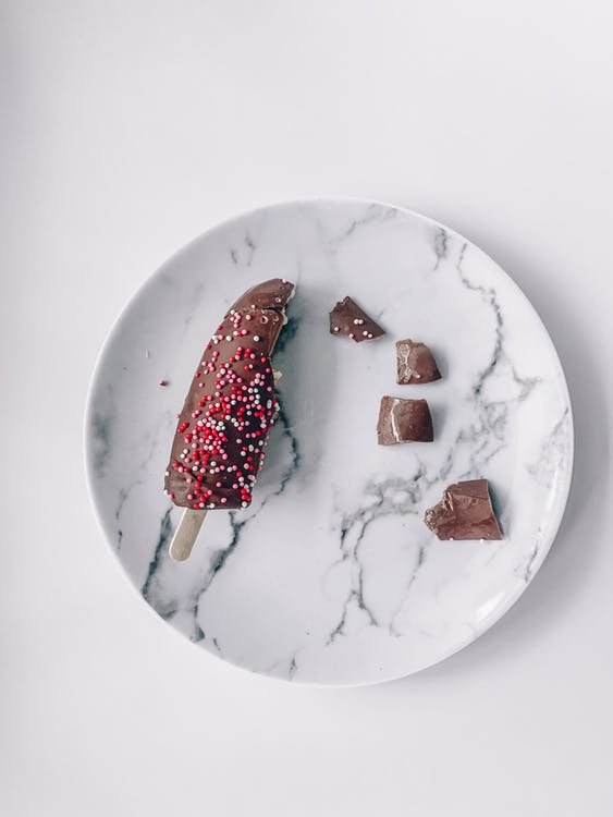 Top view of pieces of delicious chocolate ice cream placed on marble plate on white table