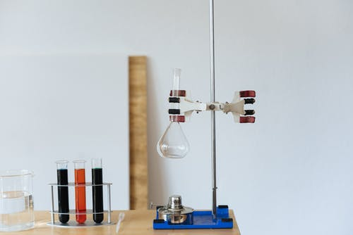 Chemical test with empty flask mounted on ring stand while burner under flask and tubes filled with reagents in modern lab