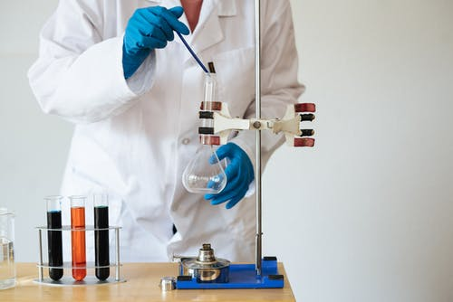 Crop of unrecognizable scientist wearing lab coat and gloves and inserting pipette into empty flask mounted on ring stand while working in laboratory