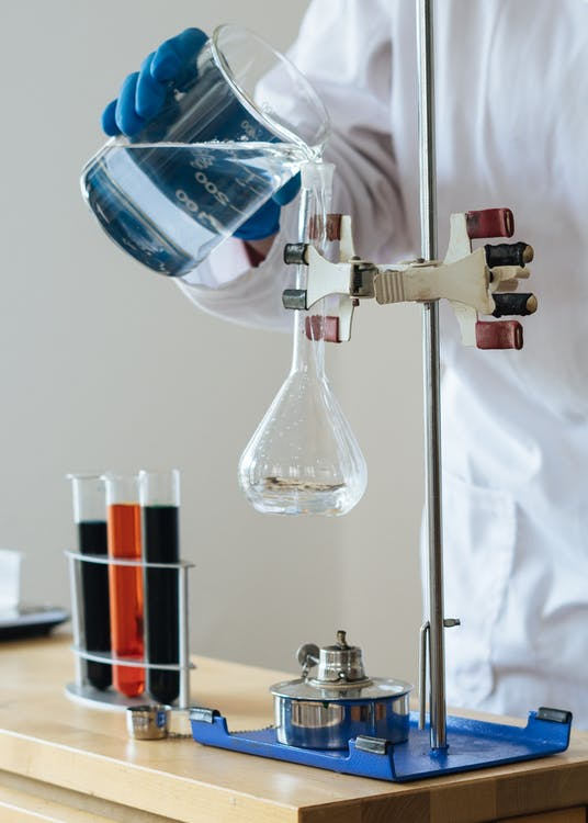 Crop chemist pouring clear liquid into fragile glassware in science center