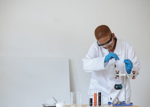 Focused African American schoolboy in safety glasses and uniform examining flask with dark liquid while conducting chemical experiment in classroom