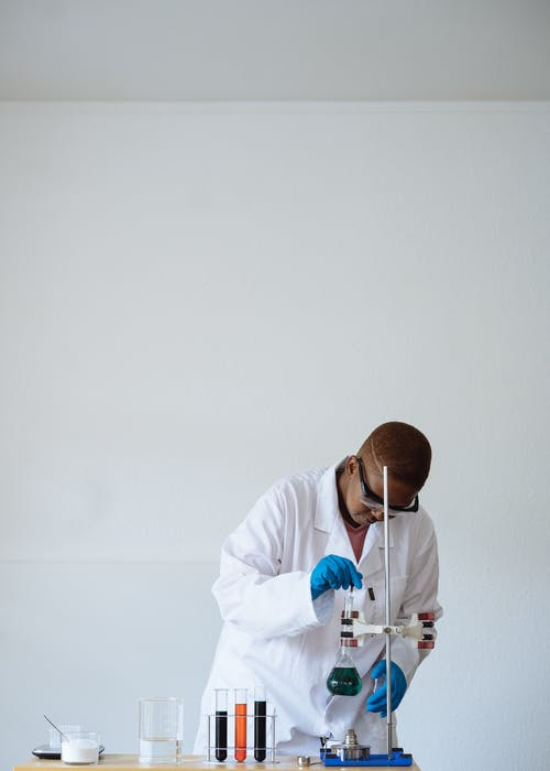 African American teen scientist in protective eyewear conducting chemical test in class