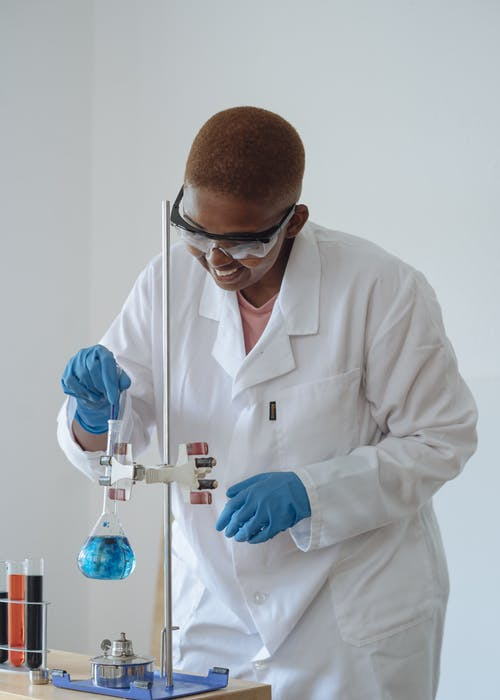 Positive African American student in protective goggles stirring light blue liquid in glassware with medical pipette while conducting experiment in science center