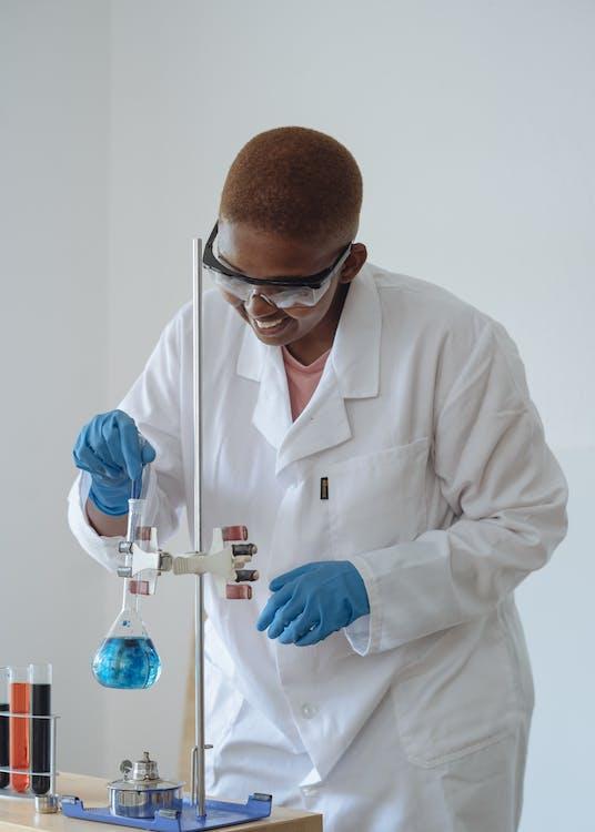 Smiling scientist examining chemical liquid in modern lab