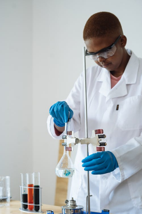 Serious scientist in uniform investigating sample while mixing reagents from different test tubes in flask mounted on stand in research center