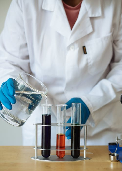 Crop of faceless researcher in uniform checking chemical reaction by pouring transparent liquid to test tubes with colored mixtures