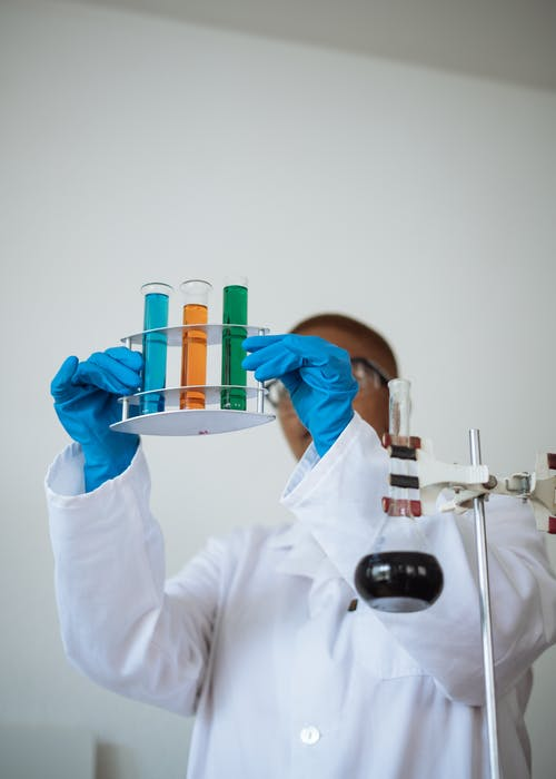 Unrecognizable African American chemist wearing uniform and analyzing chemical reaction while holding stand with test tubes in hands in modern lab