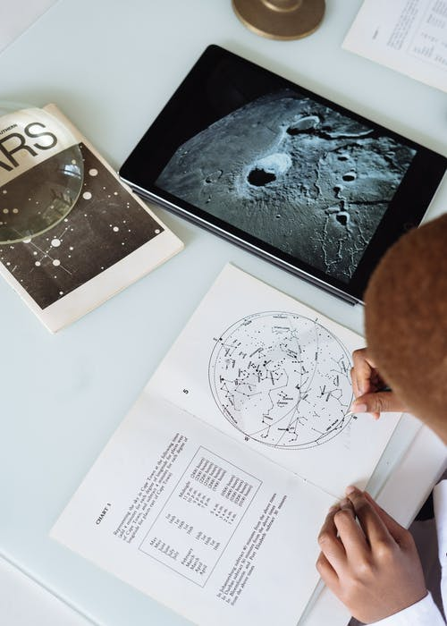 Crop of  faceless astronomer in uniform modifying astronomical map while sitting at table with tablet and educational materials conducting research at science center
