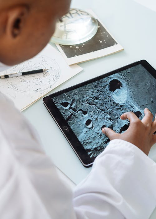 Crop astrophysicist exploring surface of moon while using tablet in university