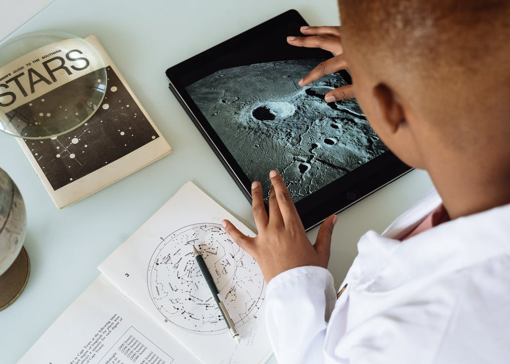 Crop African American student studying craters of moon on tablet at observatory