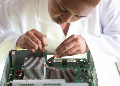 Concentrated African American technician wearing lab coat and conducting expertise of motherboard by using screwdrivers while working in service center