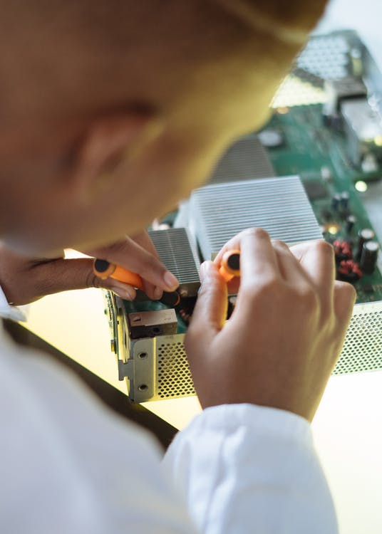 Crop of ethnic system administrator in uniform using screwdrivers and checking motherboard on electronic equipment during work in repair department