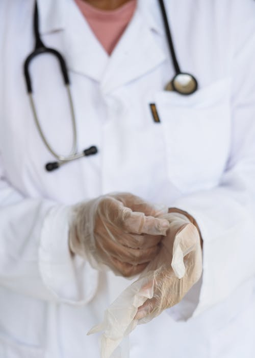 Faceless ethnic medical worker in lab coat and stethoscope taking of transparent gloves after approaching patients for examination in modern hospital