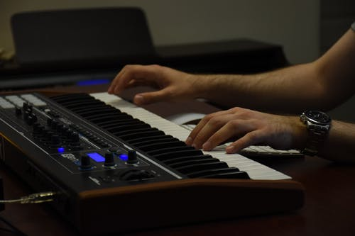 Person Playing Black and White Electric Piano