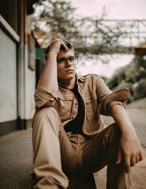 Man in Brown Coat Wearing Black Framed Eyeglasses Sitting on Concrete Floor
