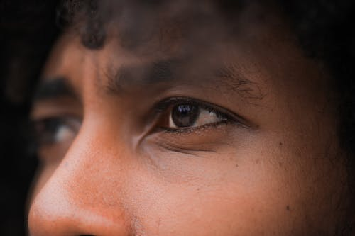 Closeup of crop anonymous pensive ethnic person with curly hair looking away thoughtfully