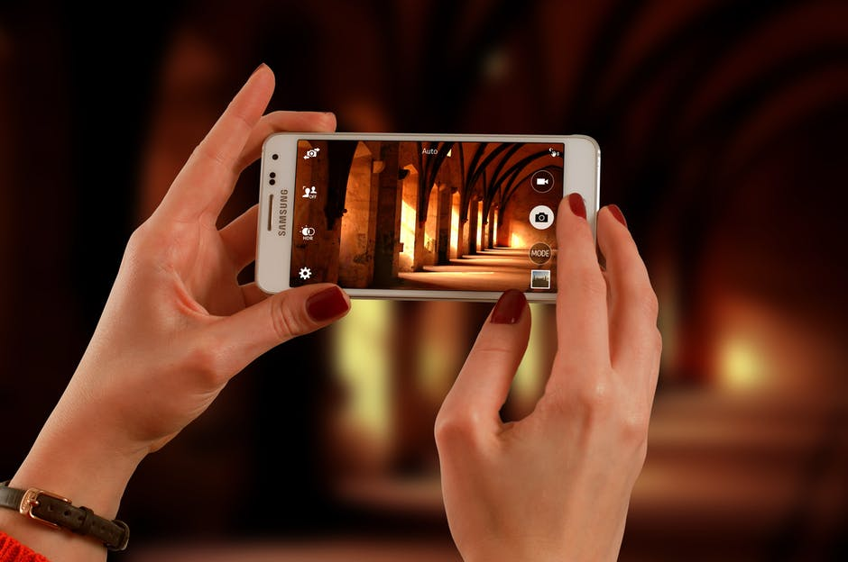 Woman Holding a White Samsung Galaxy Android Smartphone Taking a Photo of Hallway
