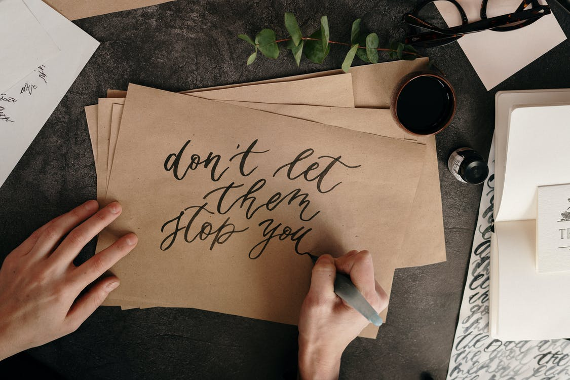 Person Writing on Brown Envelopes