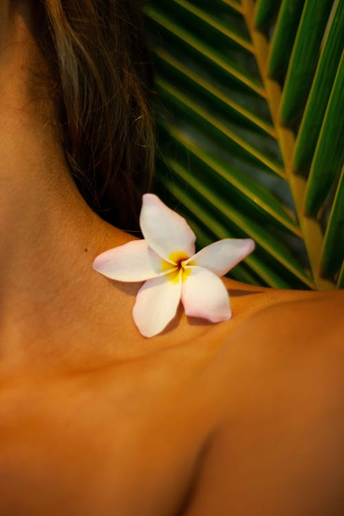 Woman With White Flower on Her Neck