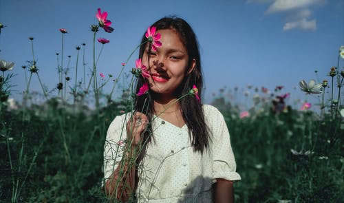 Smiling Asian woman holding stems of flowers on nature