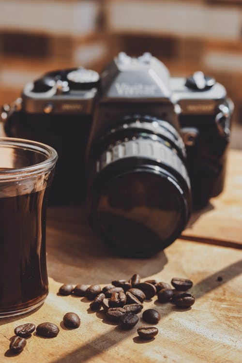 Black and Silver Nikon Dslr Camera Beside Glass Full of Coffee