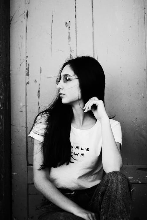 Black and white contemplative slim young brunette wearing casual outfit siting against weathered wall and touching hair while looking away thoughtfully