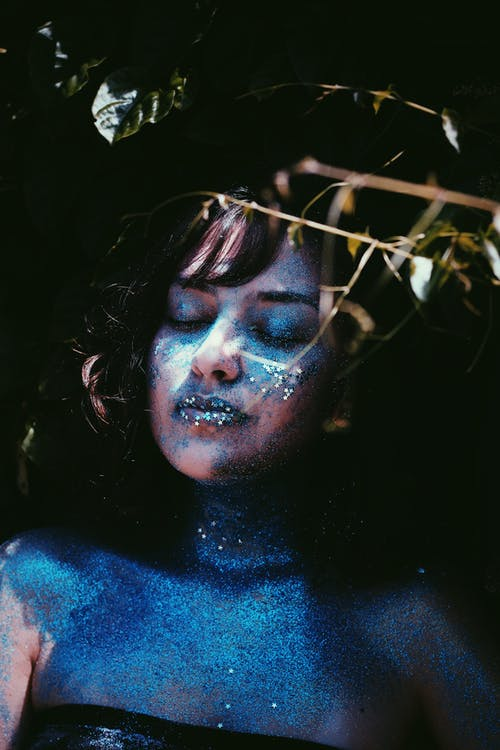 Relaxed female model with eyes closed standing with blue glittering paint on skin and dramatic makeup in studio near plant twigs