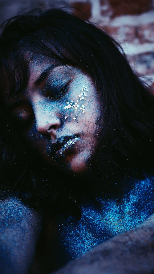 Woman's Face Covered With Blue Glitters
