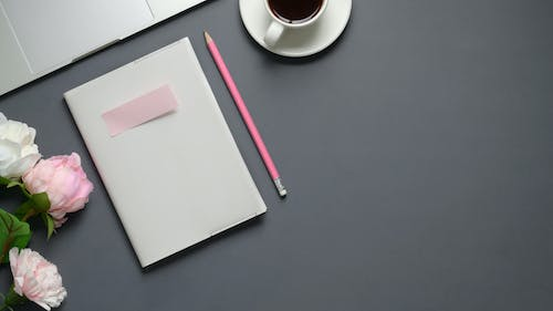 Tabletop with white notebook and pencil