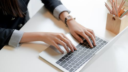 Crop woman typing on laptop keyboard in office