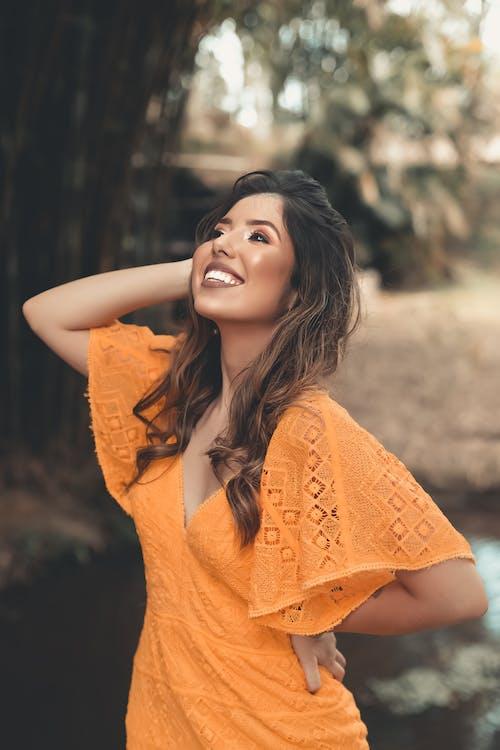Woman In Orange Dress Smiling