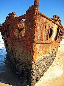 Brown Metal Shipwreck on Seashore during Daytime