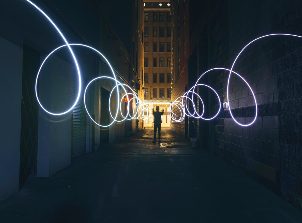 Long exposure full body person silhouette making circles with bright flashlight while standing on narrow dark city street between tall urban buildings