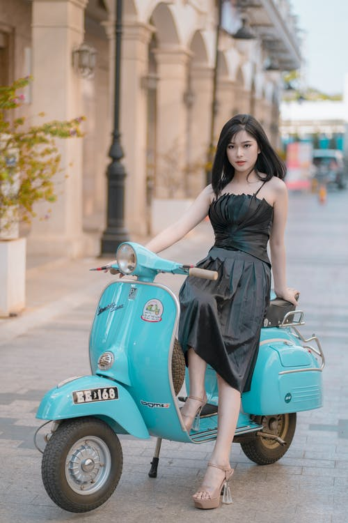 Woman in Black Sleeveless Dress Riding Blue Motor Scooter