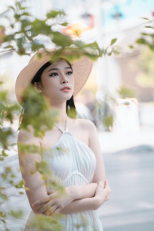 Mujer En Vestido Halter Blanco Y Sombrero De Sol Marrón