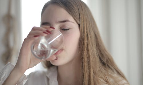 Woman in White Shirt Drinking Water From Clear Glass with Her Eyes Closed