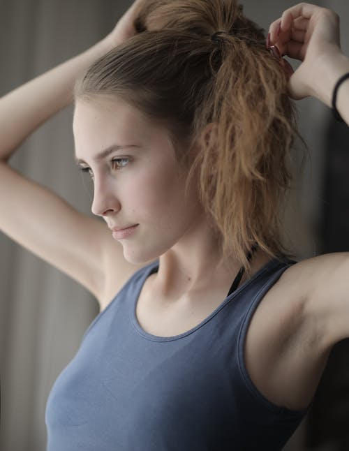 Side view of young female with natural beauty in gray t shirt with brown hair making ponytail and looking forward seriously