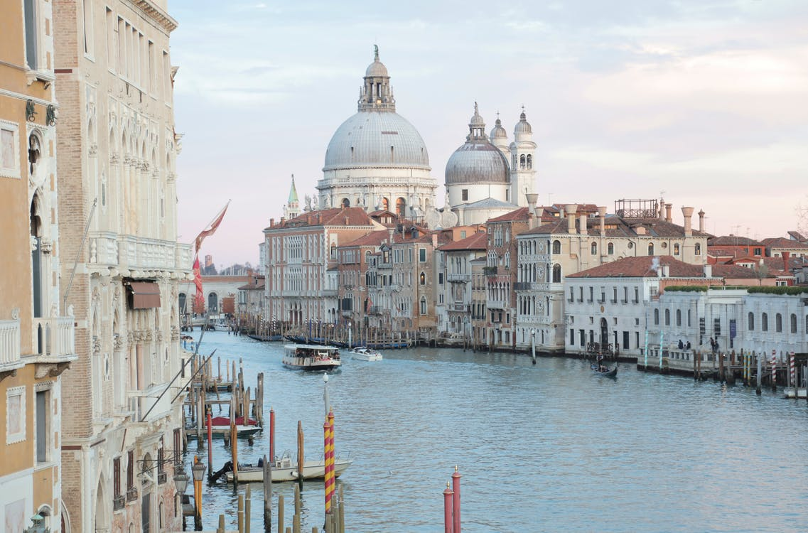 View of grand canal and old cathedral of Santa Maria della Salute in Venice in Italy on early calm morning